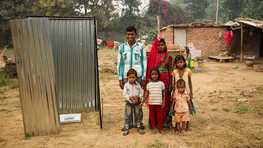 A family stands in front of a GFA-installed latrine