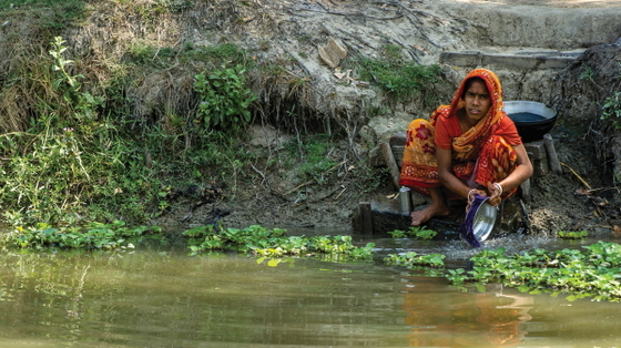 Many people in Asia, like this woman, must use unsafe water from ponds or old wells, like those in Pastor Jabez's village.