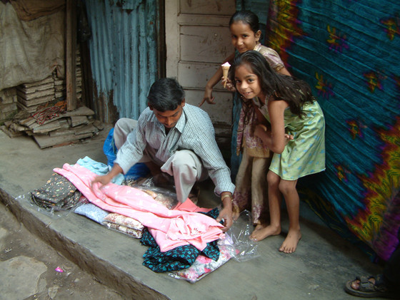 Hasan works as a cloth vendor in an Asian slum, just like this man.