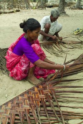 A woman weaves a coconut branch into a mat.