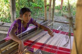 Mising women are known for their traditional costumes, and this young lady continues the custom of weaving colorful cloth.