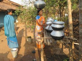 A woman readies the pots for her outdoor kitchen before preparing the evening meal.