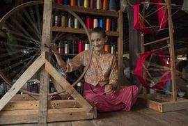 This woman is weaving thread to make cloth. The East Myanmar Region is known for its beautiful, handwoven textiles.
