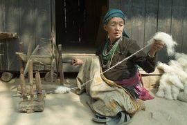 A woman in the East Nepal Region spins wool, which came from one of the sheep raised in this region.