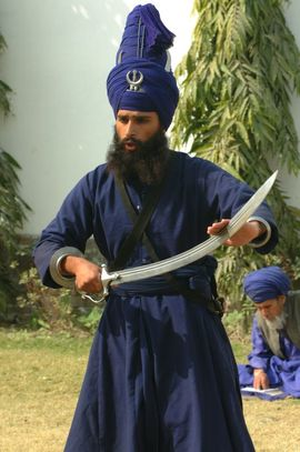 A Sikh dressed in traditional attire demonstrates the sword that is part of his spiritual discipline.