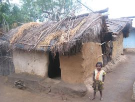This little girl is standing in front of a typical tribal home in the Jeypore Orissa Region.