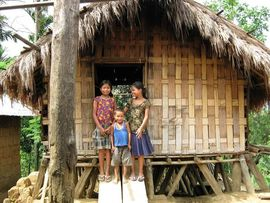 These children are standing in front of a typical tribal home, made of bamboo and leaves.