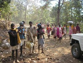A group of tribals en route to a market encounters a modern jeep on a forest road in the Northeast Madhya Pradesh Region.