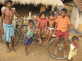 Children from the Northwest Jasidih Region eagerly pile on a man's bicycle rickshaw to pose for a photo.