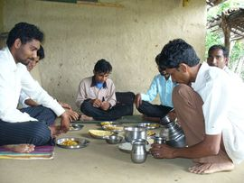 These men are eating simple meal of rice, vegetables and roti (bread) at a home in Panchmahal.