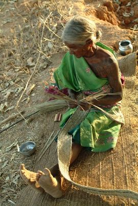 The people of Chhattisgarh are known for their ability to craft useful and decorative items from straw and bamboo. This woman shows her skill at weaving a straw mat.