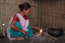 A Satgaon woman is shown lighting a fire in preparation for cooking a meal for her family.