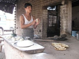 A chef in the South Punjab Region prepares roti bread and tandoori for customers at a roadside café.