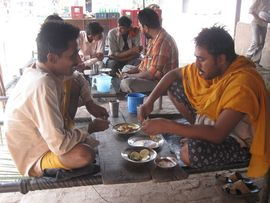 Punjabi men share a meal of dal, a stew made of lentils, peas or beans, and roti, an unleavened flatbread.