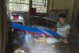 Most women and girls in the South Tripura Region are skilled at weaving. This lady weaves a bright blanket that will be sold in the village market.