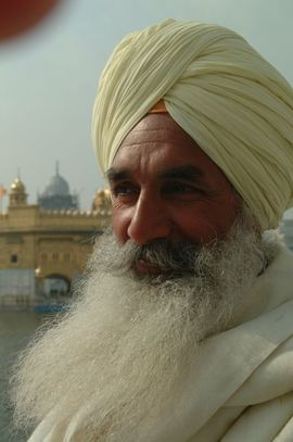 A Sikh man with the traditional beard and unique turban stands in front of the Golden Temple in Amritsar, Southwest Punjab.