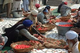 Sikh volunteers prepare vegetables for a meal for the poor outside the gates of the Golden Temple.
