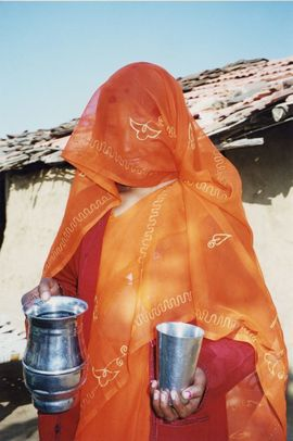 A Bhil woman in her native dress offers water to a visitor.