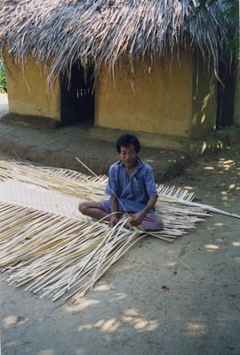 This tribal villager begins the task of making an elaborate bamboo basket.