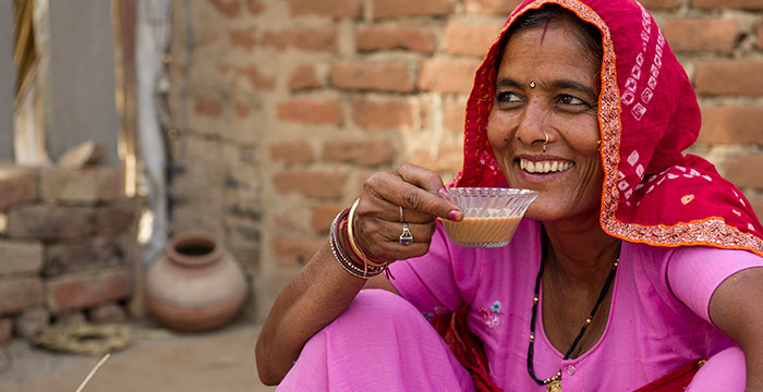 Widow drinking chai and smiling.