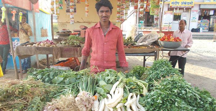 Man standing beside his vegetable cart