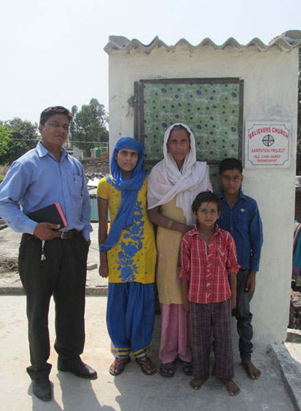 family beside a GFA World toilet given to them
