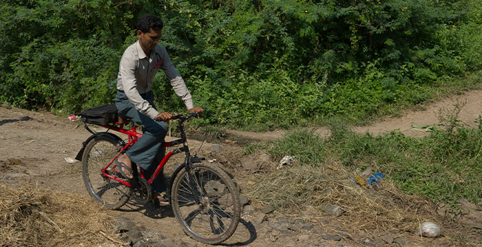 GFA national worker riding a bicycle over rough terrain.