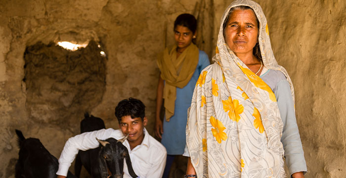 A widow beside her children and a goat she was given from GFA World.