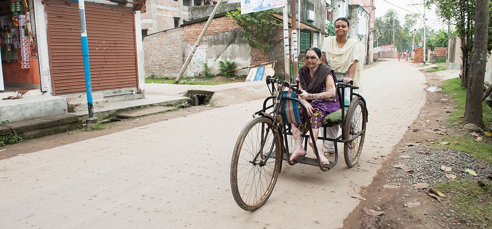 With an adult tricycle, Priya is able to leave her shanty.