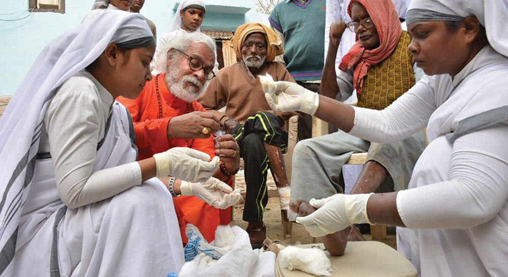 K.P. Yohannan helps clean wounds of leprosy patients