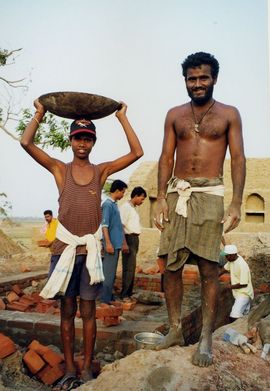 Homes in the Bhubaneswar Region are often constructed of brick and mud. The young boy is carrying mortar on the plate on his head.
